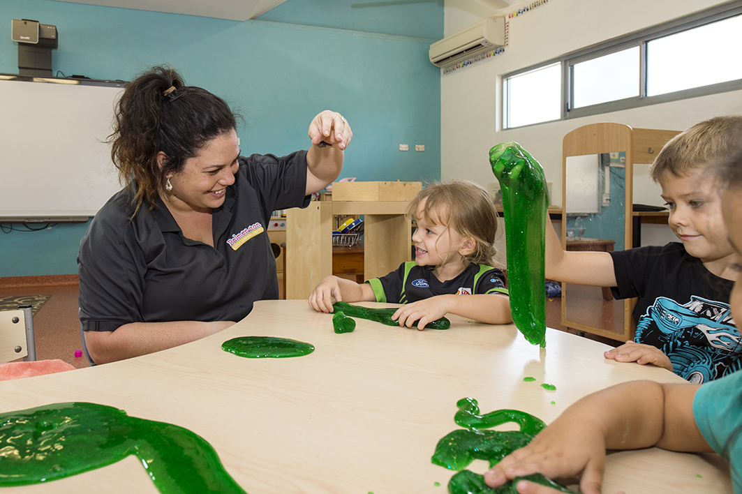 Group of children and child care educator playing with slime at Milestones Palmerston