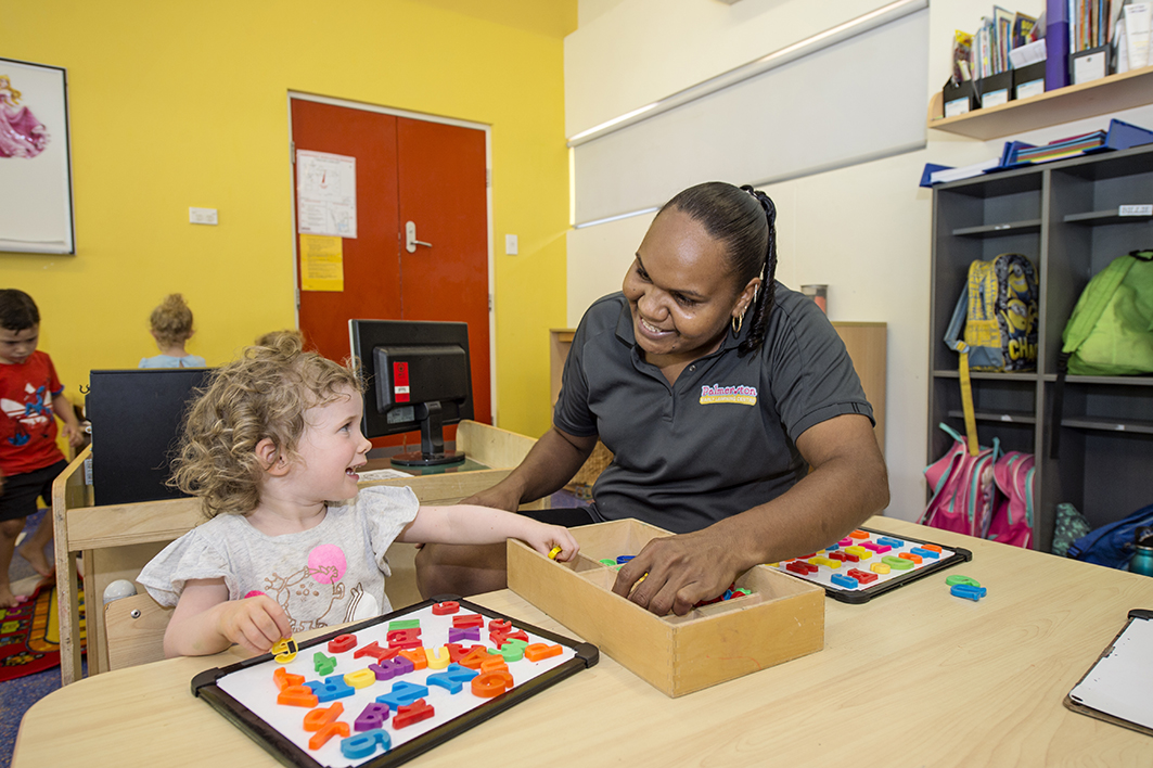 Child care educator helping child with puzzle at Milestones Palmerston